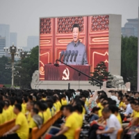 Chinese President Xi Jinping, shown on a large screen, delivers a speech during celebrations of the 100th anniversary of the founding of the Communist Party of China at Tiananmen Square in Beijing on Thursday.  | AFP-JIJI