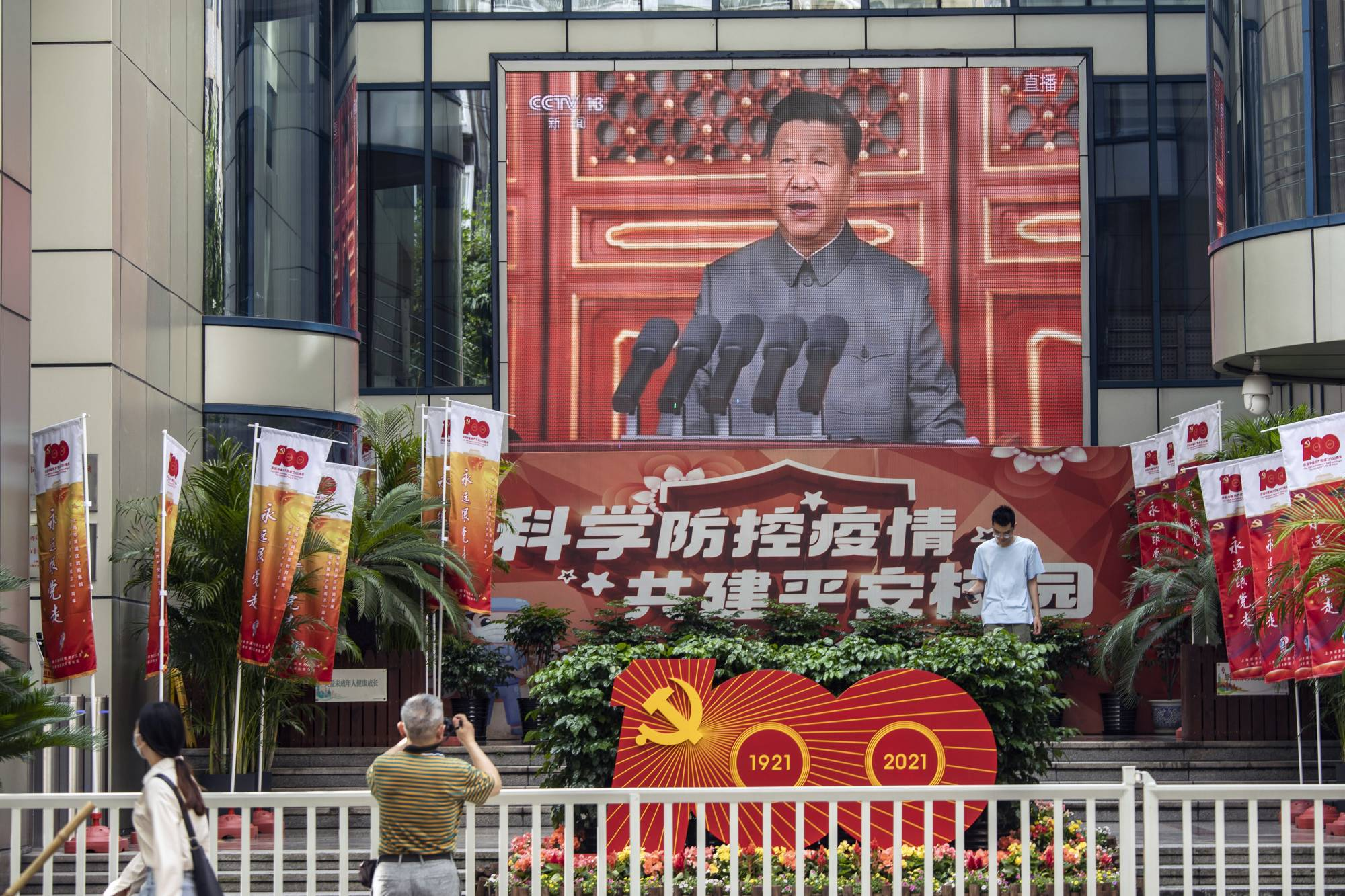 A screen in Shanghai on Thursday shows a live news broadcast of Chinese President Xi Jinping speaking at a ceremony marking the centenary of the Chinese Community Party, taking place at Beijing's Tiananmen Square.   BLOOMBERG