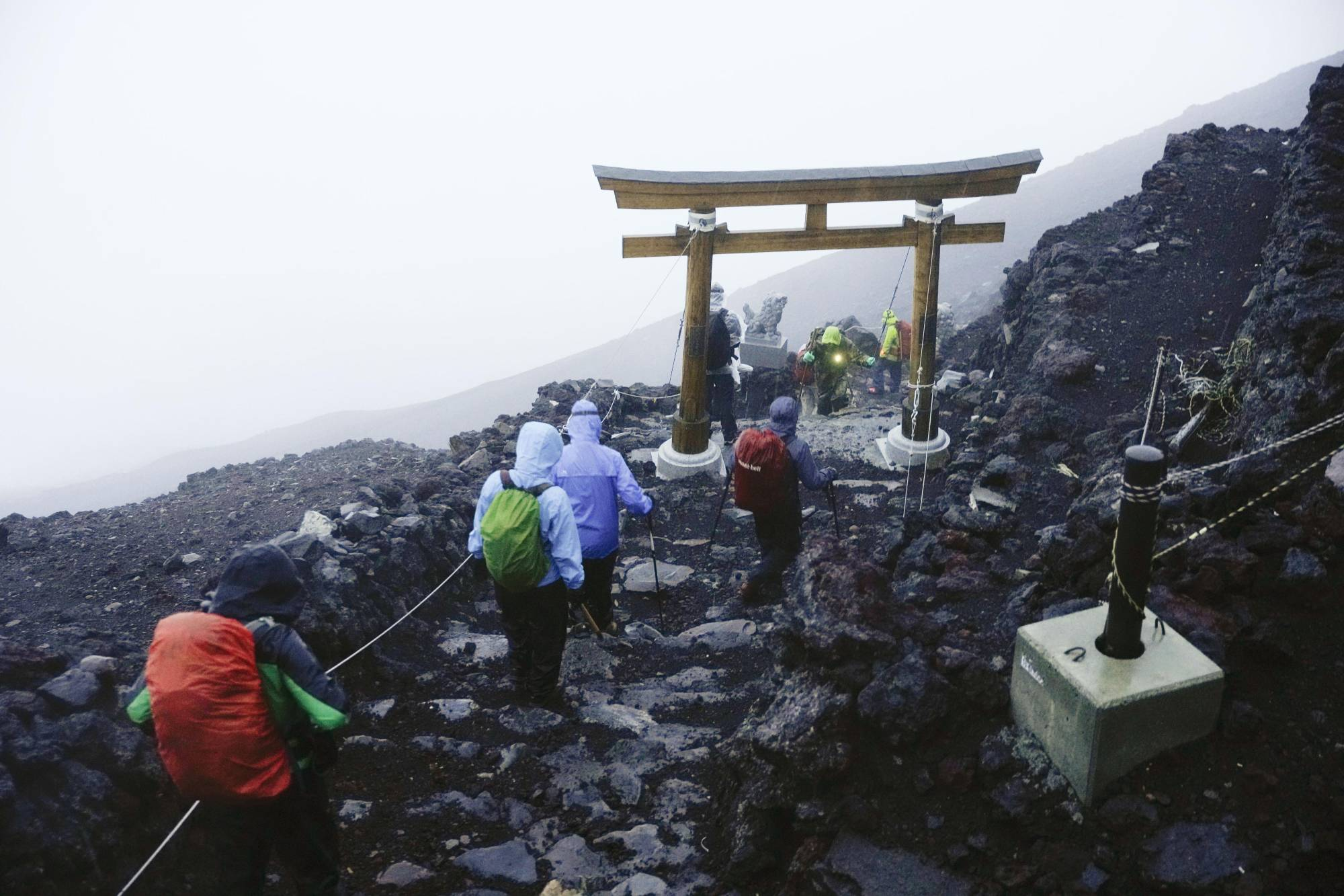 Climbers who made it to the summit of Mount Fuji head back down amid bad weather early Thursday.   KYODO