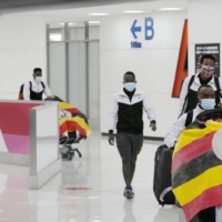 Members of Uganda's Olympic team leave Narita Airport after a member of the team tested positive for COVID-19 and was barred entry into Japan, near Tokyo on June 20.   KYODO