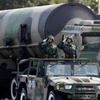 People's Liberation Army soldiers salute in front of nuclear-capable missiles during a parade in Beijing in 2009.    REUTERS