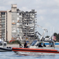 U.S. Coast Guard and Miami-Dade Police patrol waters near a partially collapsed condo in Surfside, Florida, on Thursday.  | REUTERS