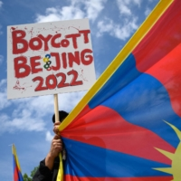 A Tibetan activist holds a placard and a Tibetan flag during a protest against the Beijing 2022 Winter Olympics in front of the Olympics Museum in Lausanne, Switzerland, on June 23.   AFP-JIJI