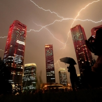 A bolt of lightning crosses the sky as people look at buildings displaying a light show in Beijing on Wednesday.   AFP-JIJI