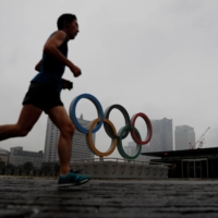 A jogger runs past newly installed Olympic rings in Yokohama on Wednesday.  | REUTERS