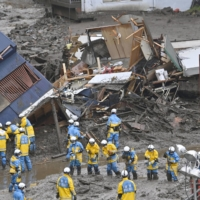 Rescue workers search for missing people in Atami, Shizuoka Prefecture, on Sunday.   KYODO