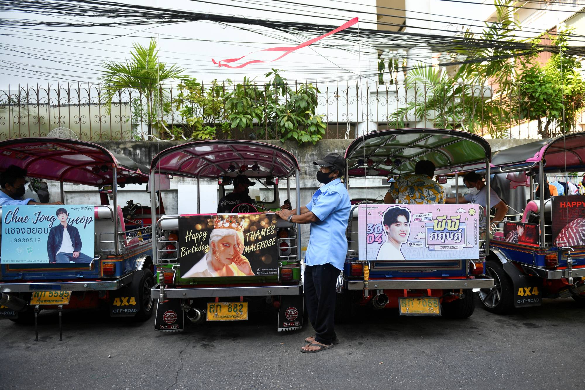 Tuk-tuk drivers, with their vehicles decorated with banners of Thai and Korean stars, wait for customers in Bangkok in May.  | REUTERS