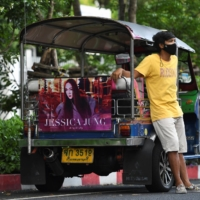 Tuk-tuk driver Samran Thammasa stands next to his vehicle, decorated with a banner of K-pop star Jessica Jung, as he waits for customers in Bangkok. | REUTERS