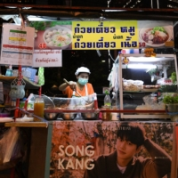 A woman selling street food has her stall decorated with a banner of Korean star Song Kang in Bangkok in April.  | REUTERS