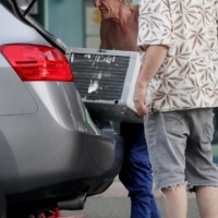 People transport an air conditioner unit in Vancouver during the heat wave on June 28.    BLOOMBERG