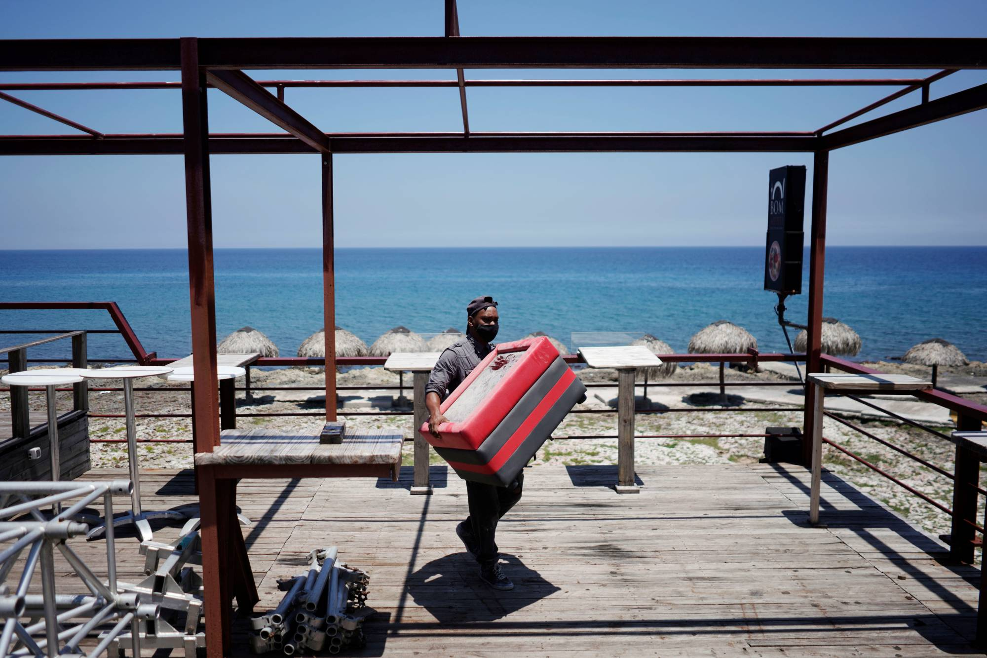 A worker removes furniture from a restaurant terrace as Storm Elsa approaches the island, in Havana on Saturday.    REUTERS