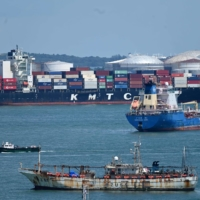 A container vessel makes its way along the Singapore Strait on June 28.   AFP-JIJI