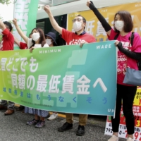 Labor union members call for raising minimum wages outside the labor ministry last month.   KYODO