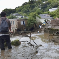 A man watches a search and rescue operation in Atami, Shizuoka Prefecture, on Monday, after Saturday's mudslides.   KYODO