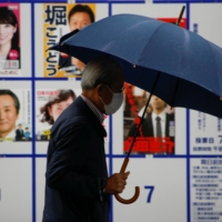 A voter walks past a board displaying posters of candidates for the Tokyo Metropolitan Assembly election near a polling station in Tokyo on Sunday.   REUTERS