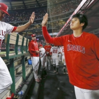 Shohei Ohtani high-fives Angels pitcher Alex Cobb after the seventh inning against the Orioles on Saturday. | KYODO