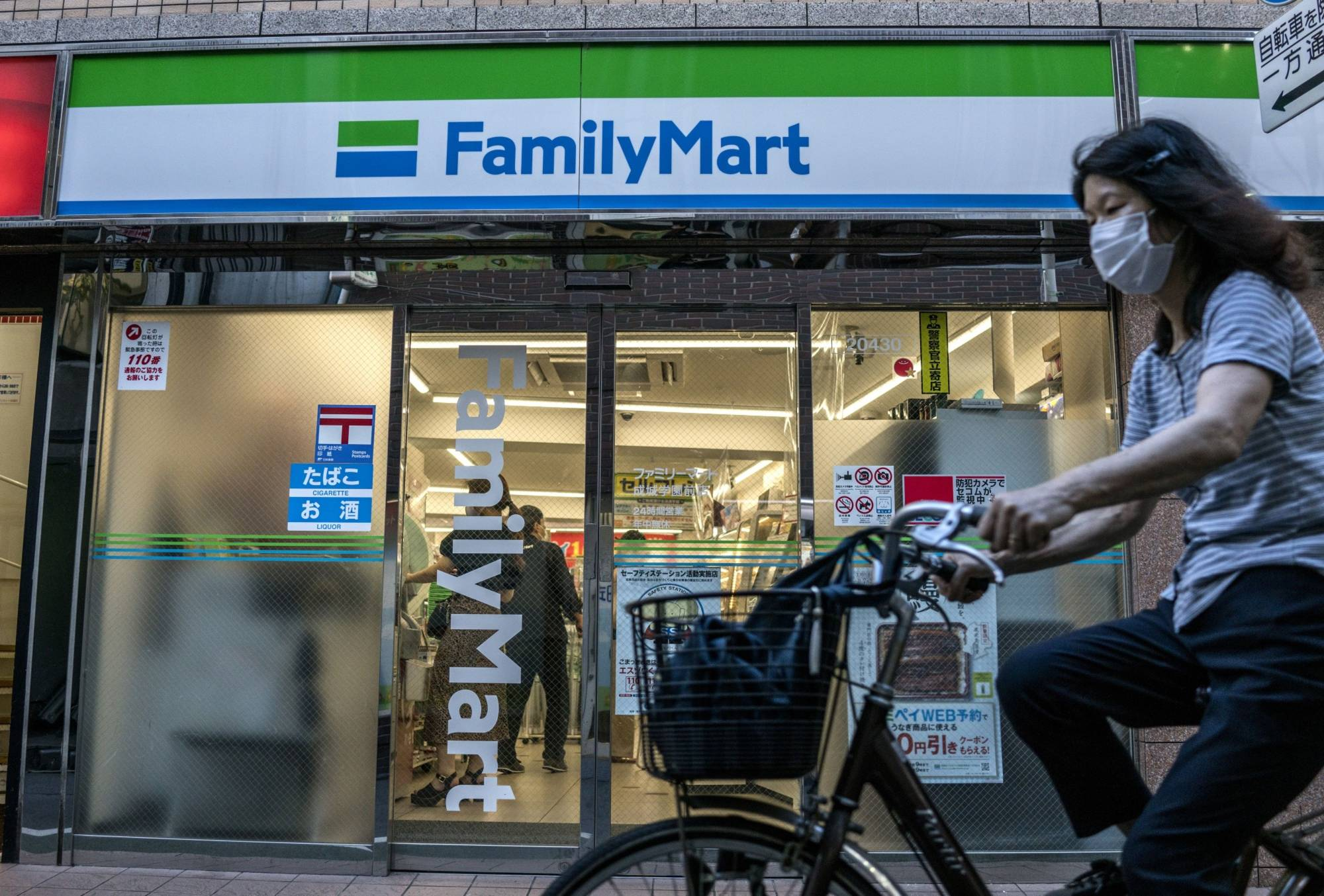 A cyclist passes a FamilyMart Co. convenience store in Tokyo in July 2020. The operator is outpacing Lawson Inc. and Seven-Eleven Japan Co. in terms of introducing labor-saving operations.   BLOOMBERG