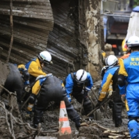 Police officers continue their search for the missing in Atami, Shizuoka Prefecture, on Tuesday, after Saturday's mudslides swept away houses and left dozens missing.   KYODO