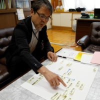 Jun Tashiro, the principal of Shiratori Elementary School, shows a chart listing problems that would need to be solved to taking students to watch the Olympic Games, during an interview at the school in Tokyo on June 30. | REUTERS