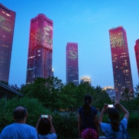 Chinese characters reading 'Never forget the original intention' and the emblem of the Chinese Communist Party illuminate buildings during a light show in Beijing on June 26.   BLOOMBERG