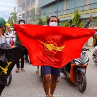 Demonstrators carry flags and display the three-finger salute during a protest against Myanmar's army ruler, Min Aung Hlaing, in Mandalay, Myanmar, on Saturday.   TIME FOR REVOLUTION / VIA REUTERS