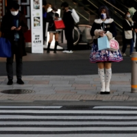 Pedestrians stand in front of a cross walk at a shopping district in Tokyo last December.   REUTERS