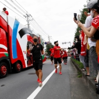 A sponsor truck and staff lead the relay before the runners' arrival during the first day of a Tokyo 2020 Olympic torch relay in Saitama Prefecture, in the city of Wako. | REUTERS