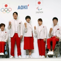 Japanese athletes model the Tokyo Olympics uniforms, which are a riff on the colors and design of the country's 1964 uniforms. | KYODO / VIA REUTERS