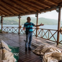 Restaurant owner Dimitar Pendoski inspects his closed restaurant on the shore of the Lake Ohrid, North Macedonia, last month. | AFP-JIJI