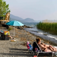 A family sunbathes on the beach near an excavator used to demolish illegal buildings in the no-build zone on the shore of the Lake Ohrid, North Macedonia, last month. | AFP-JIJI