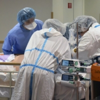 Medical workers treat a severely ill COVID-19 patient at Kindai University Hospital in Sayama, Osaka Prefecture, in August. | KINDAI UNIVERSITY HOSPITAL / VIA KYODO