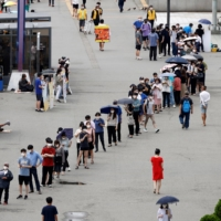 People wait in line for a COVID-19 test in Seoul on Wednesday.    REUTERS