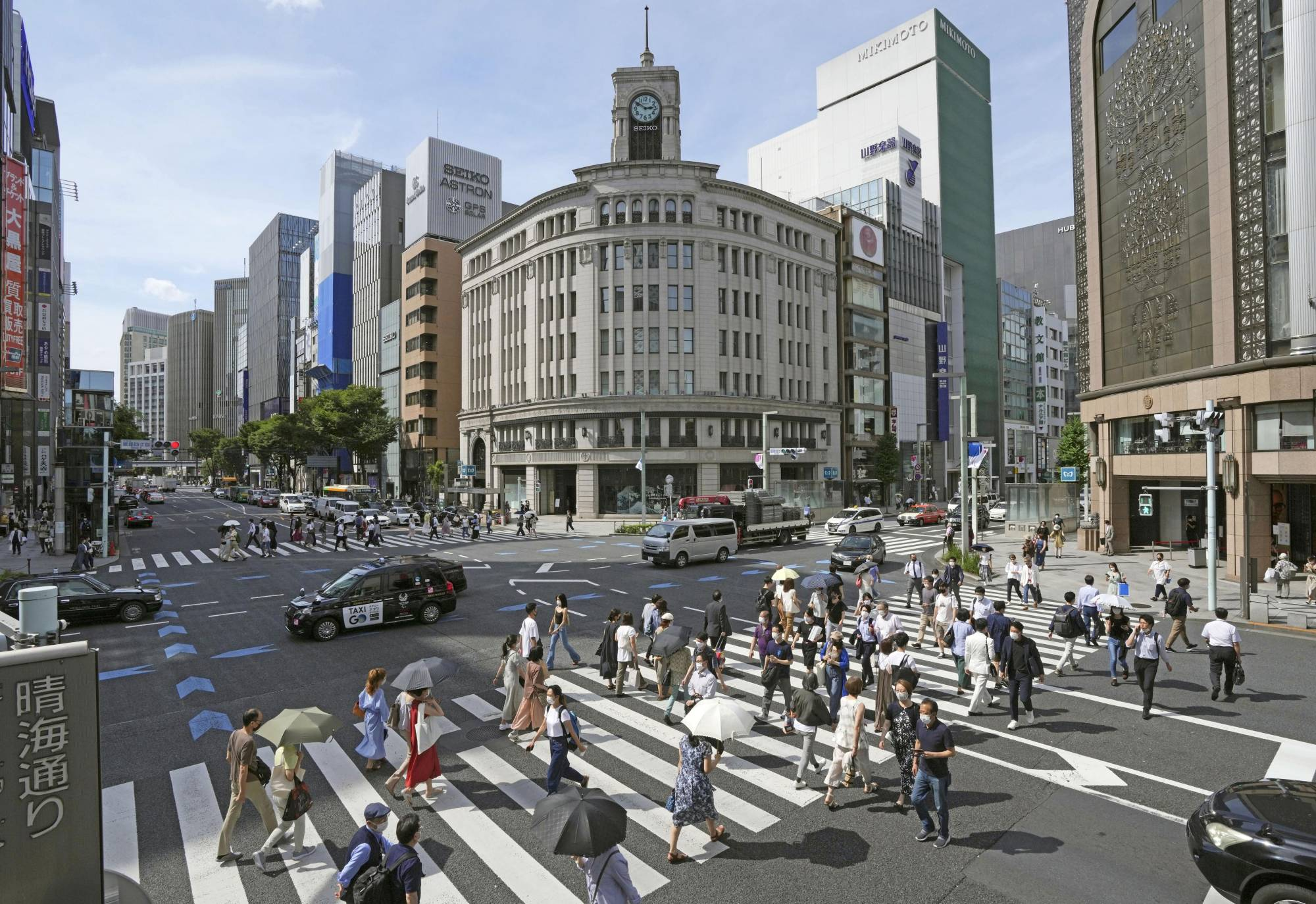 People walk in Tokyo's Ginza shopping district on June 28. The government is considering extending its COVID-19 quasi-emergency for Tokyo and three neighboring prefectures for about a month until early August, sources said Wednesday. | KYODO