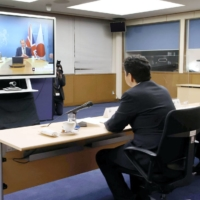 Foreign Minister Toshimitsu Motegi (front right) and Defense Minister Nobuo Kishi hold a videoconference with their British counterparts Dominic Raab (right on the screen) and Ben Wallace on Feb. 3. | POOL / VIA KYODO