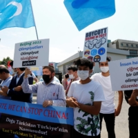 Ethnic Uyghur demonstrators take part in a 'No Beijing 2022' protest in front of the headquarters of Turkey's National Olympic Committee, in Istanbul.   REUTERS