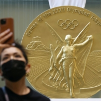 A visitor takes a photo in front of a 2.5-meter gold medal displayed at a building in Tokyo's Chuo Ward on Monday.  | KYODO