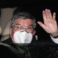 IOC President Thomas Bach waves after arriving at his hotel in Tokyo on Thursday.   POOL / VIA REUTERS