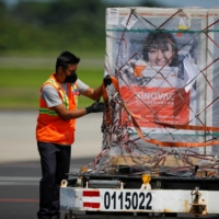An air carrier worker unwraps a container of China's Sinovac COVID-19 vaccines at the Oscar Arnulfo Romero International Airport in San Luis Talpa, El Salvador, on Wednesday.   REUTERS