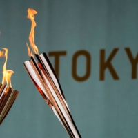 Torches are displayed during a lighting ceremony in Tokyo on Friday after the torch relay on a public road was canceled due to the COVID-19 pandemic. | REUTERS