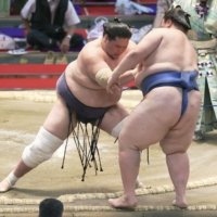 Terunofuji (left) shoves out Ichinojo during their bout at the Nagoya Grand Sumo Tournament on Friday.   KYODO