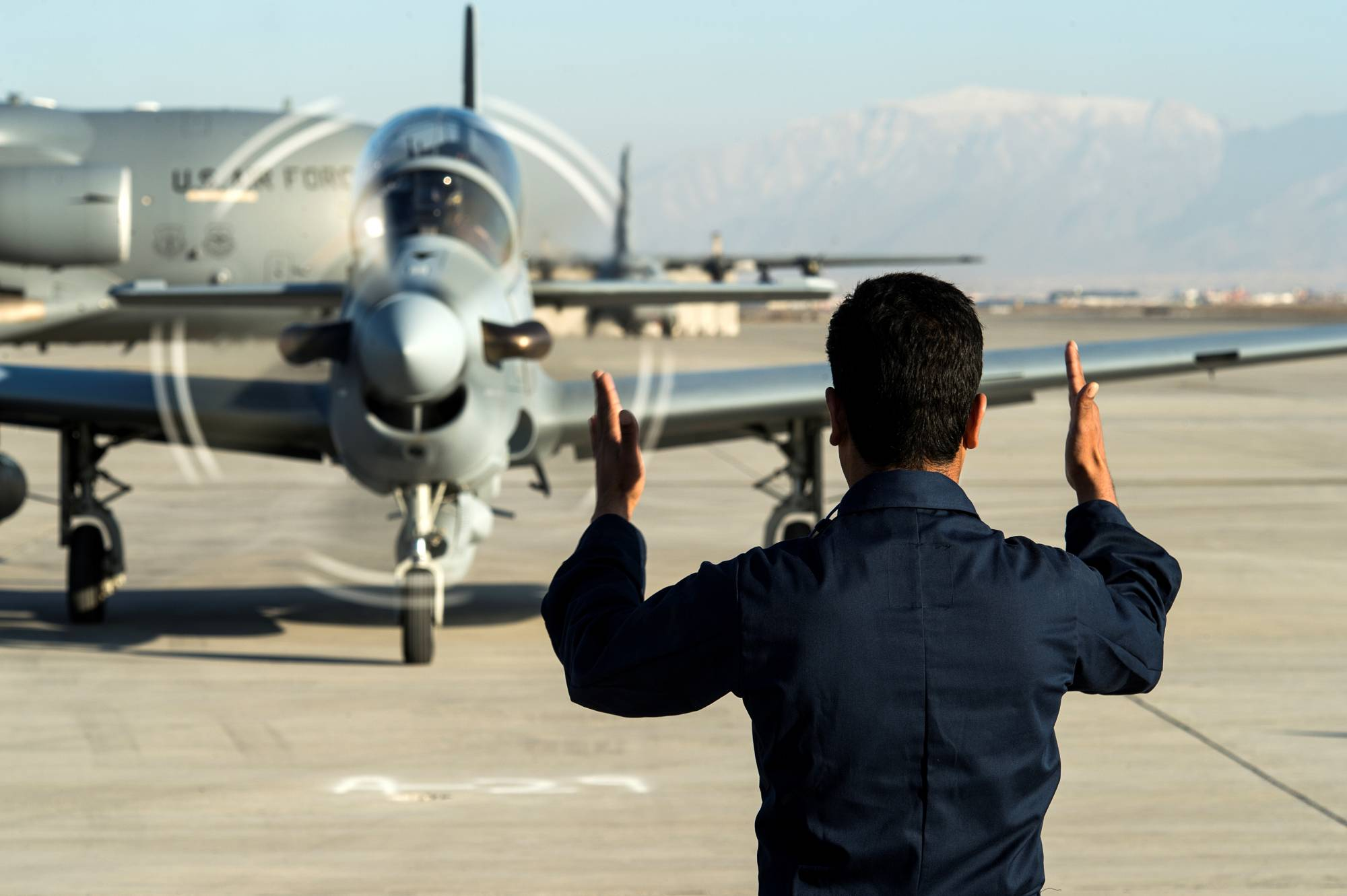 A member of the Afghan Air Force signals to an A-29 Super Tucano at Hamid Karzai International Airport near Kabul in January 2016.   U.S. AIR FORCE / VIA REUTERS