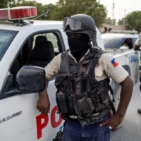 Haitian national police guard the entrance to the U.S. Embassy as people gather to ask for asylum following the assassination of President Jovenel Moise, in Port-au-Prince, on Friday. | REUTERS