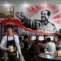 People eat in front of an image of late Chinese communist leader Mao Zedong at a restaurant in Shaoshan, in China's central Hunan province, on May 26.    AFP-JIJI