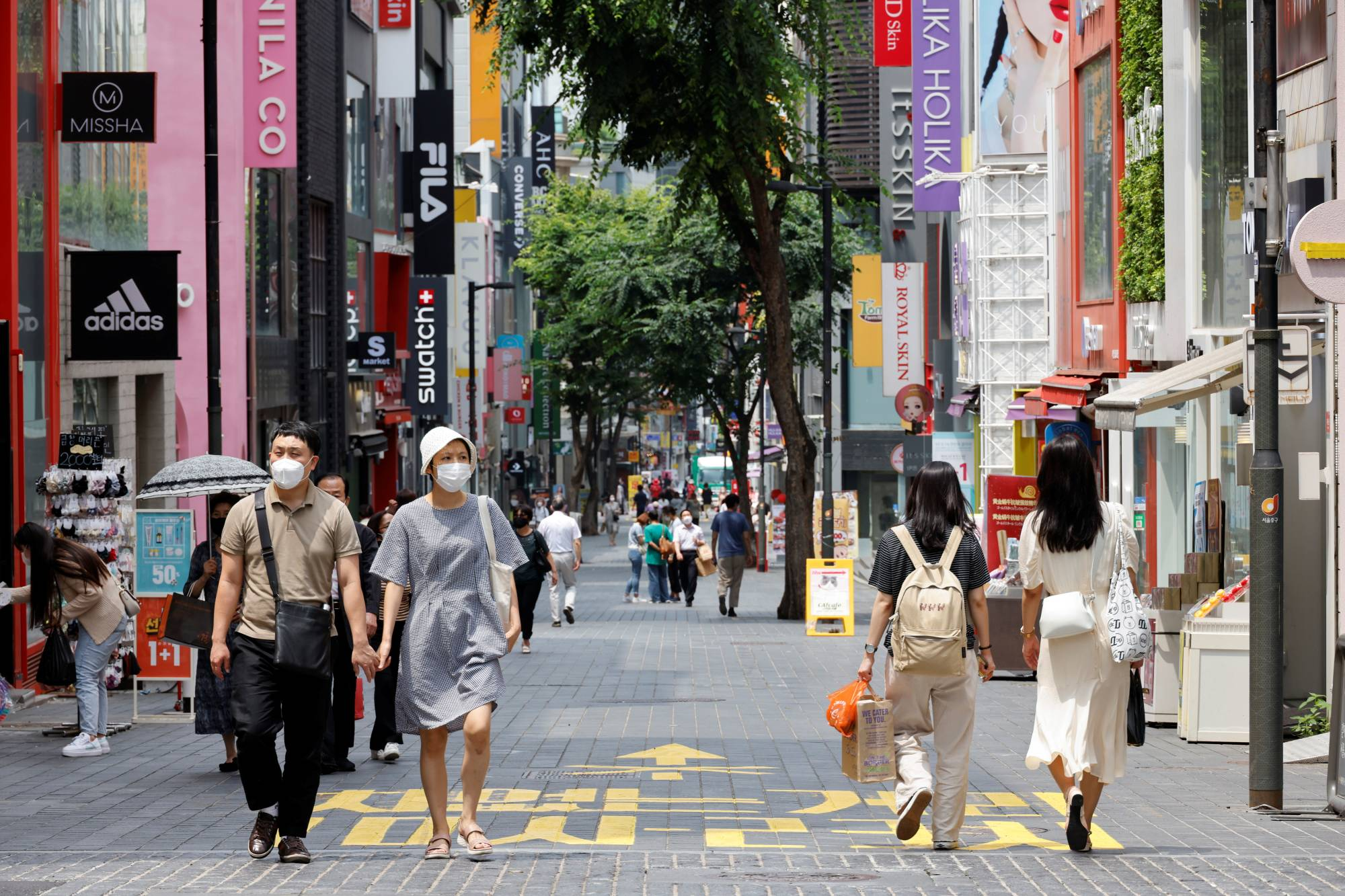 People wearing masks walk in a shopping district in Seoul on Friday.   REUTERS