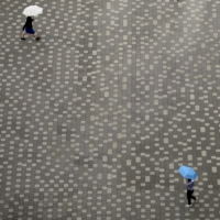 Socially distanced people, holding umbrellas in the rain, walk across a square in Tokyo's Koto Ward on Friday. | REUTERS