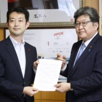 Chiba Gov. Toshihito Kumagai submits a request to education minister Koichi Hagiuda calling for the scrapping of the system that requires teachers to renew their licenses every 10 years at a meeting last month in Tokyo. | KYODO