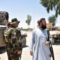 Afghan security personnel stand guard along a road amid ongoing fighting with Taliban fighters in Kandahar on Friday. | AFP-JIJI
