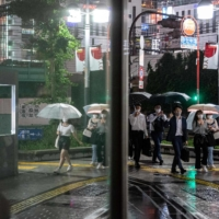 People walk on a street in Tokyo's Shinjuku district as Japan announces a new virus state of emergency stretching throughout the Tokyo Olympics on Thursday.    AFP-JIJI