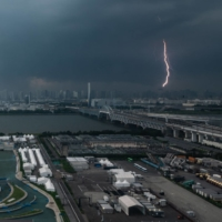 A bolt of lightning is seen in the background past the Kasai Canoe Slalom Center, the main venue for canoe slalom during the Tokyo 2020 Olympics in the capital on Sunday. | AFP-JIJI