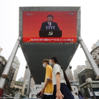 A speech by Chinese President Xi Jinping in shown on a big screen in Beijing on July 1. | REUTERS